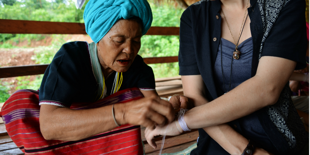 White string being tied around a woman's arm, a traditional Karen practise.