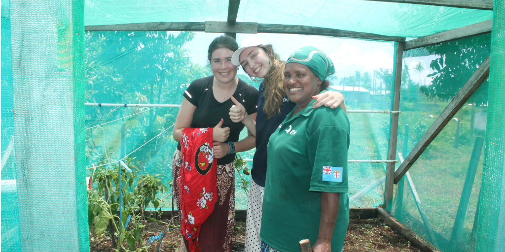 Two GVI volunteers standing next to a woman from Dawasamu in a plant shelter constructed out of wood and shade cloth.