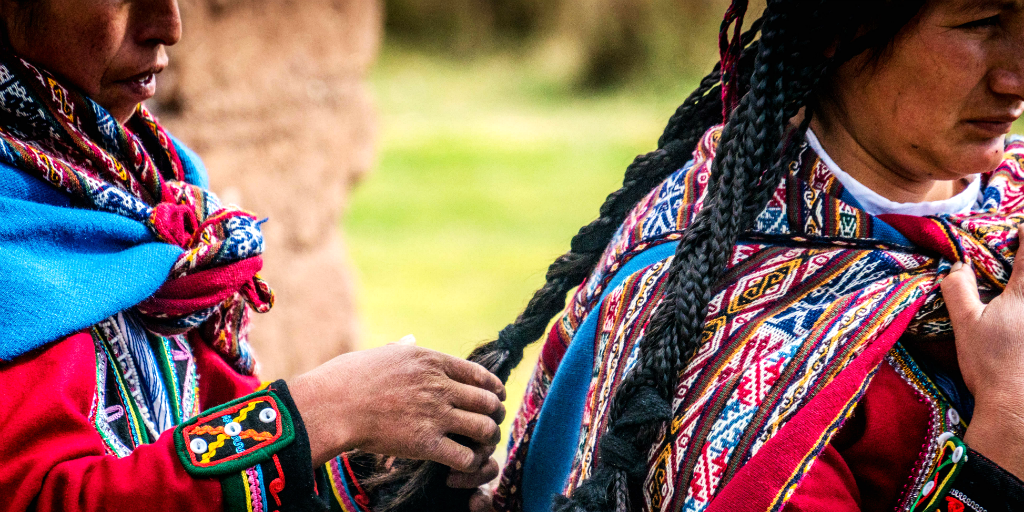 A Peruvian woman braiding another Peruvian woman's hair, both dressed in traditional Peruvian clothing.