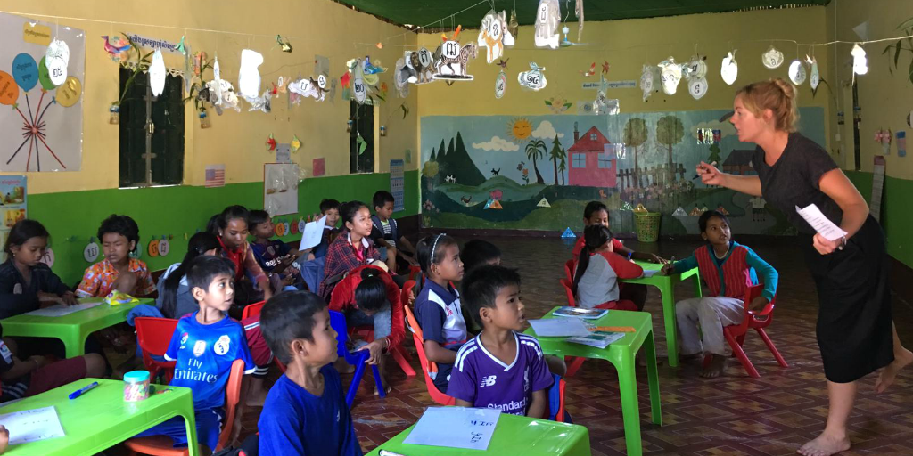 A volunteer teacher teaching a class of young children in Cambodia