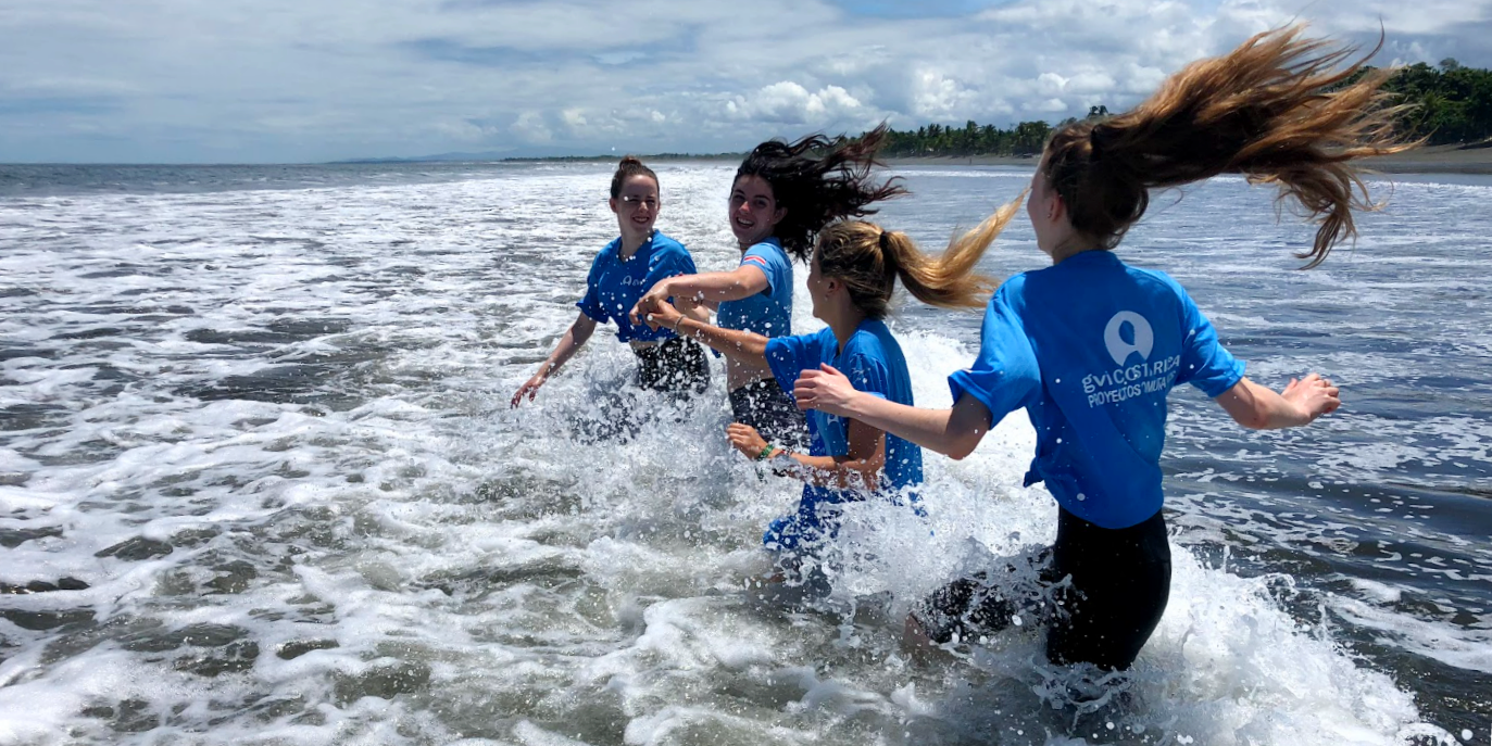 Under 18 participants splash through waves in Costa Rica.