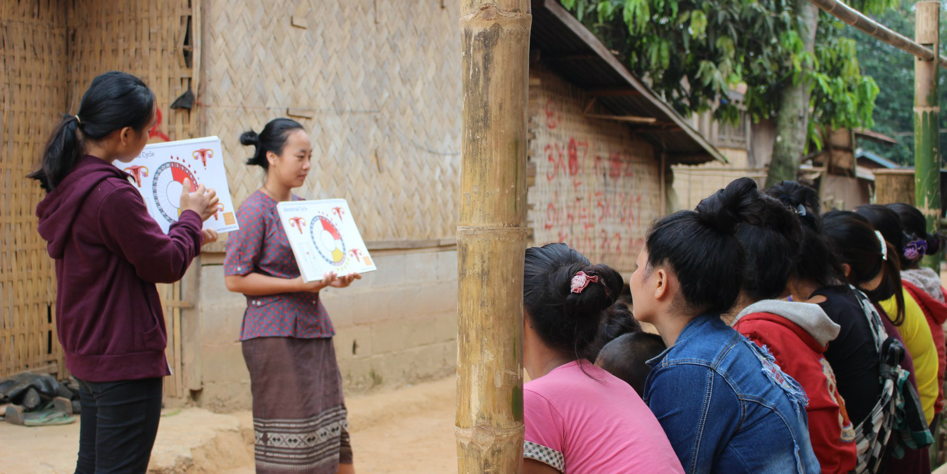 Pay to volunteer with GVI, and your program fees go toward increasing local capacity. Pictured: Two local women from Laos conduct a menstrual health workshop in a rural village.