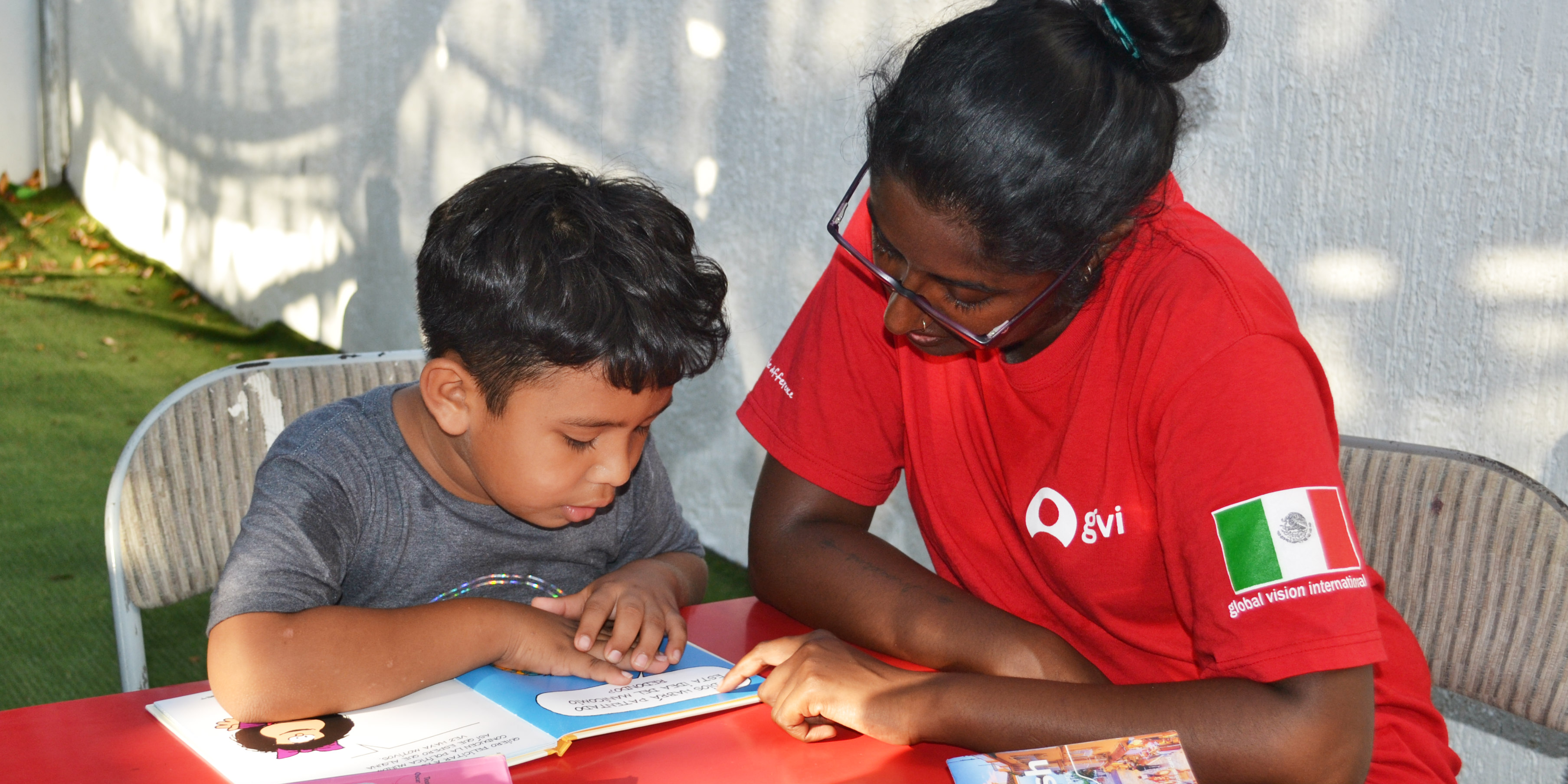 A GVI participant works with a child on their reading, while volunteering in Mexico.