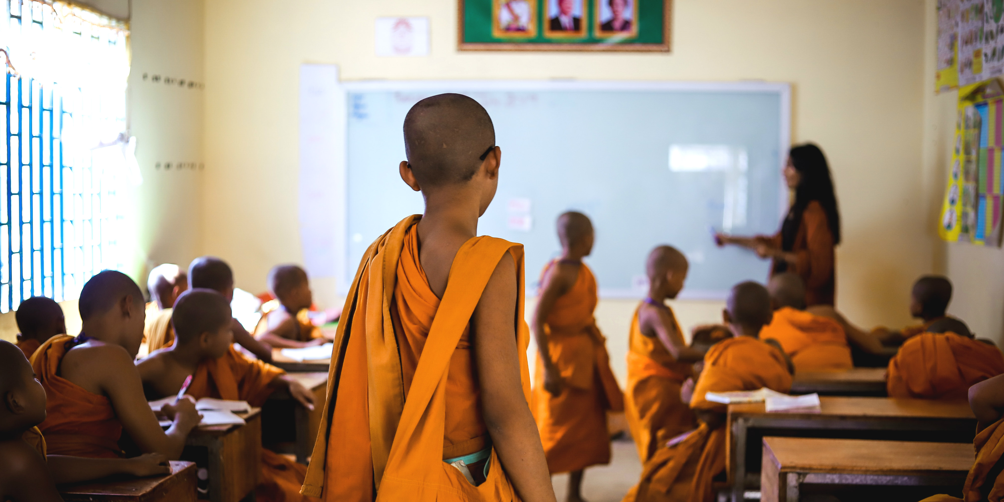 A novice monk enters an English lesson in Cambodia. This program, which is one of the best volunteer abroad programs for adults, seeks to increase educational capacity in Kampong Cham.