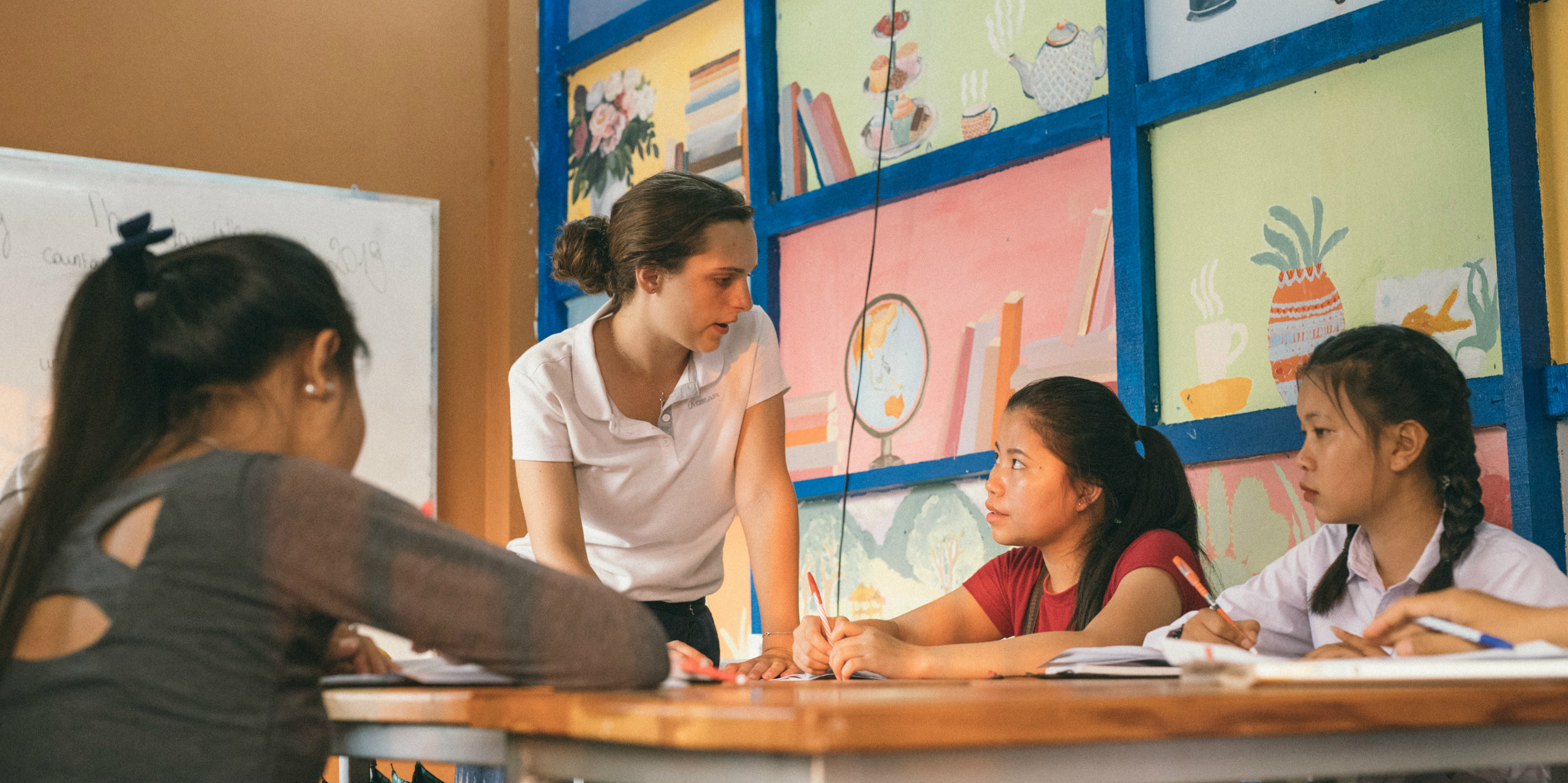 A GVI participant engages with women learners while on a volunteer teaching program.