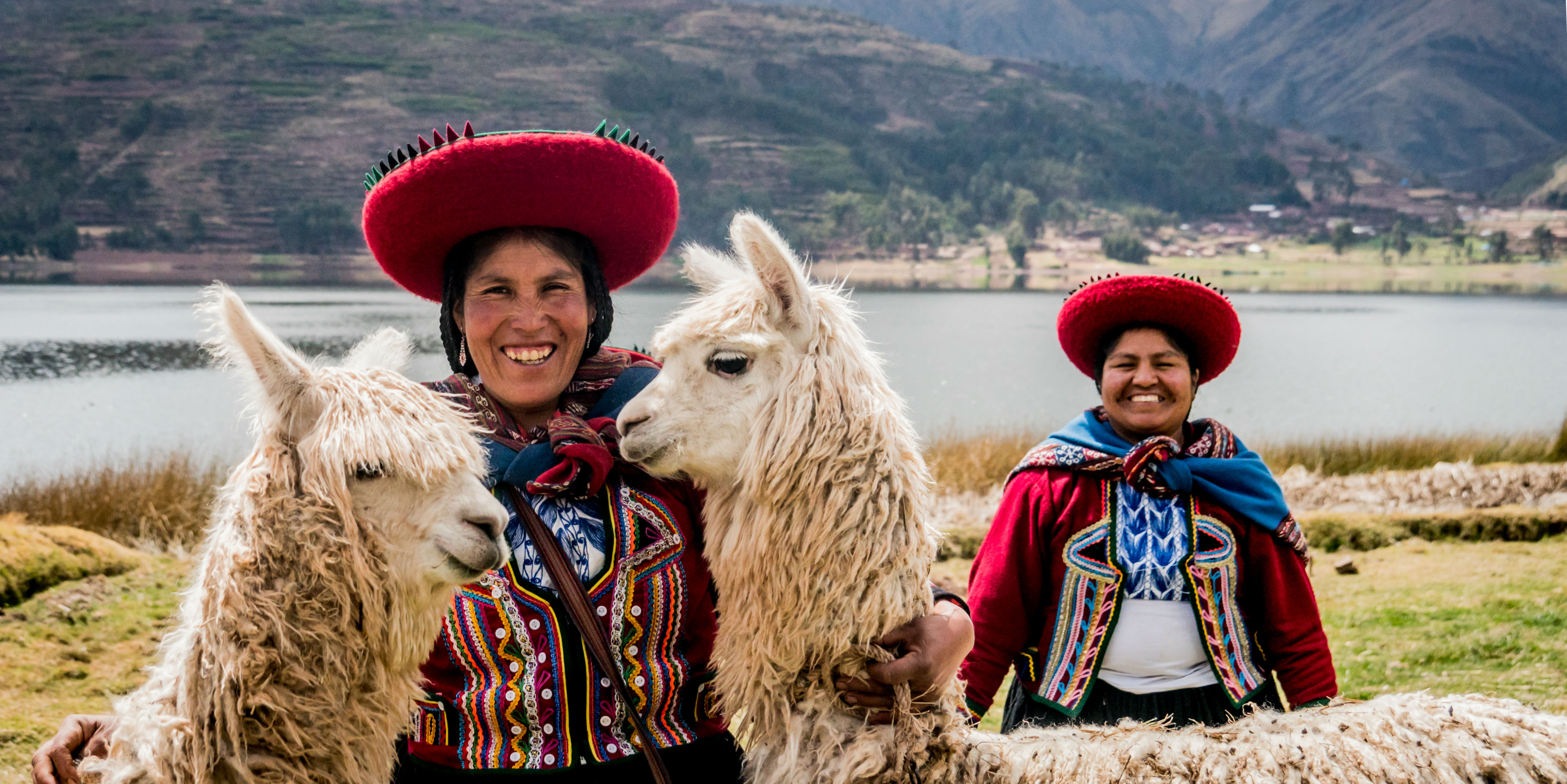 Two women in Cusco pose, while dressed in Andean-styled clothing. Cusco is one the places where you'll have opportunities to see quechua culture in Peru.