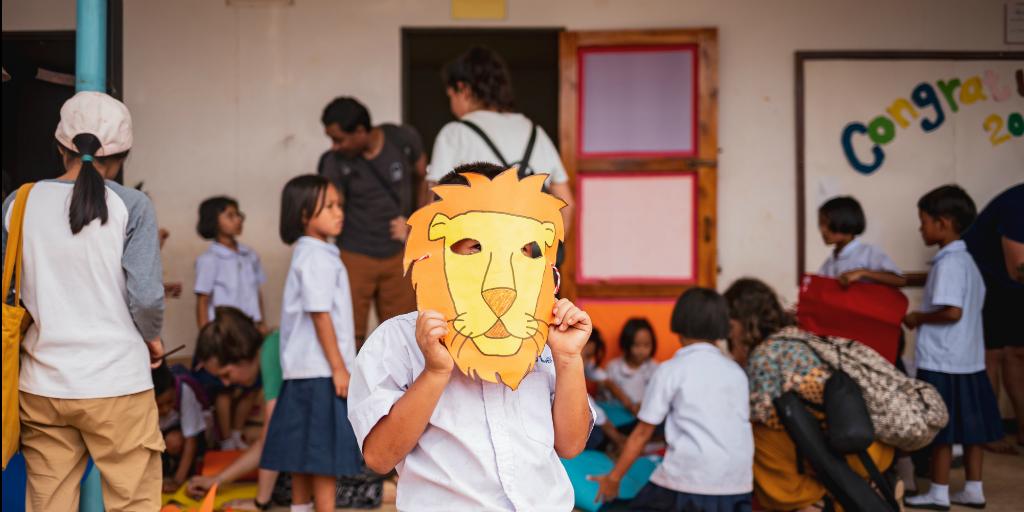 A child wearing a lion mask