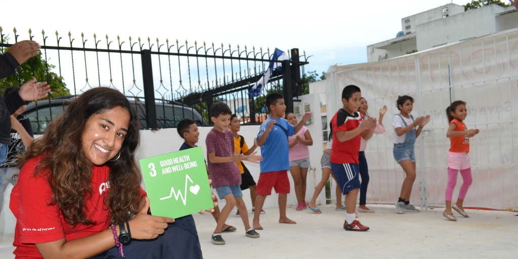 GVI volunteer holding up a SDG infront of a kids exercise class