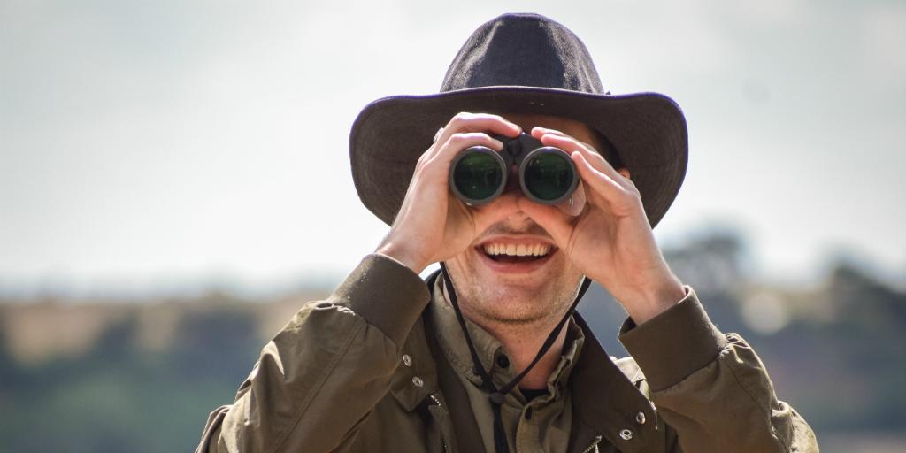 Wildlife volunteer looking into the distance with binoculars