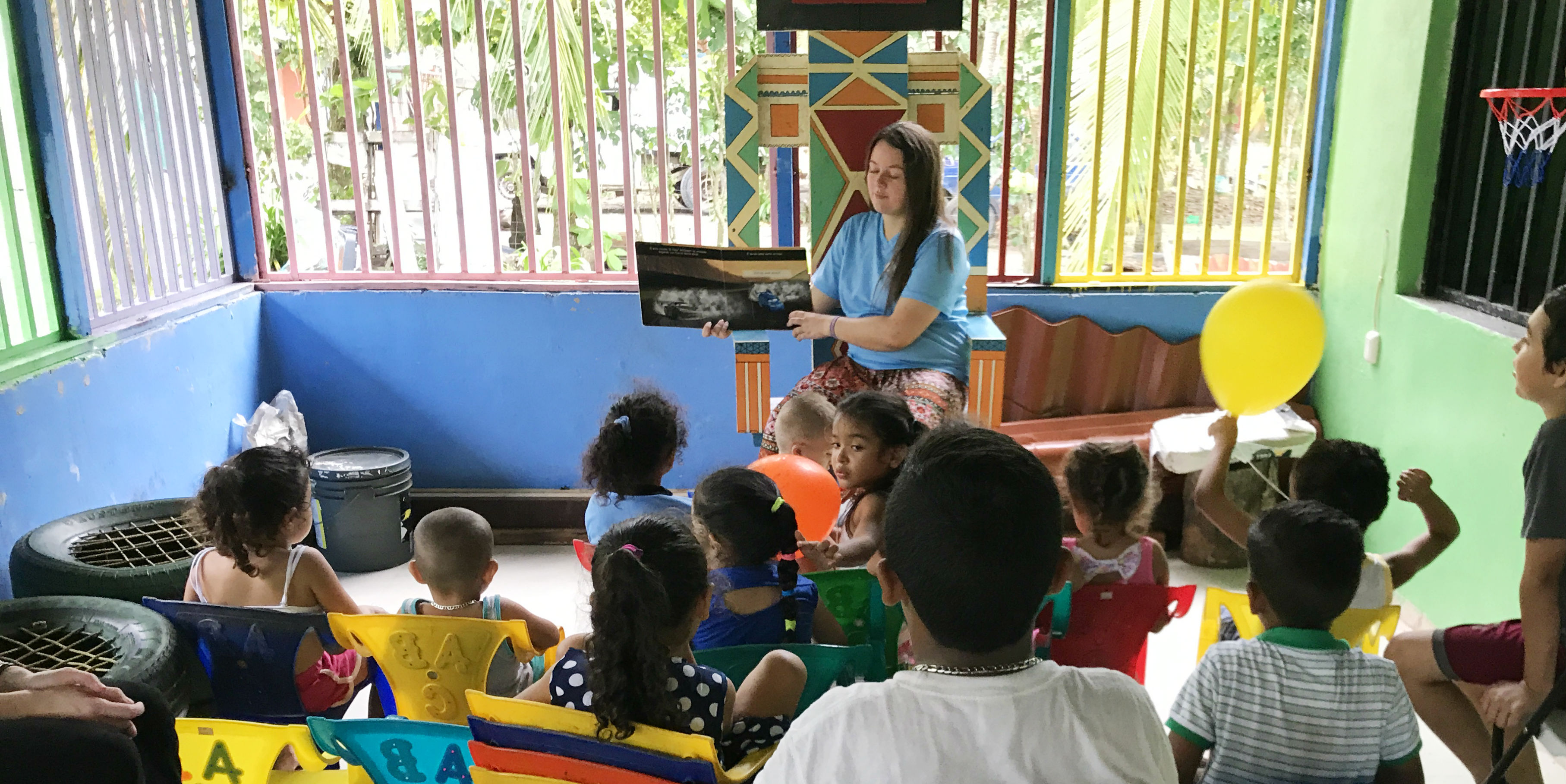 A gap year volunteer reads to children in Costa Rica.