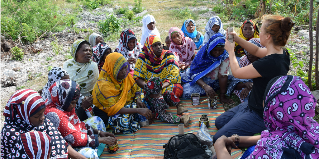 A volunteer doing a seed planting demonstration with women in Kilimanjaro.