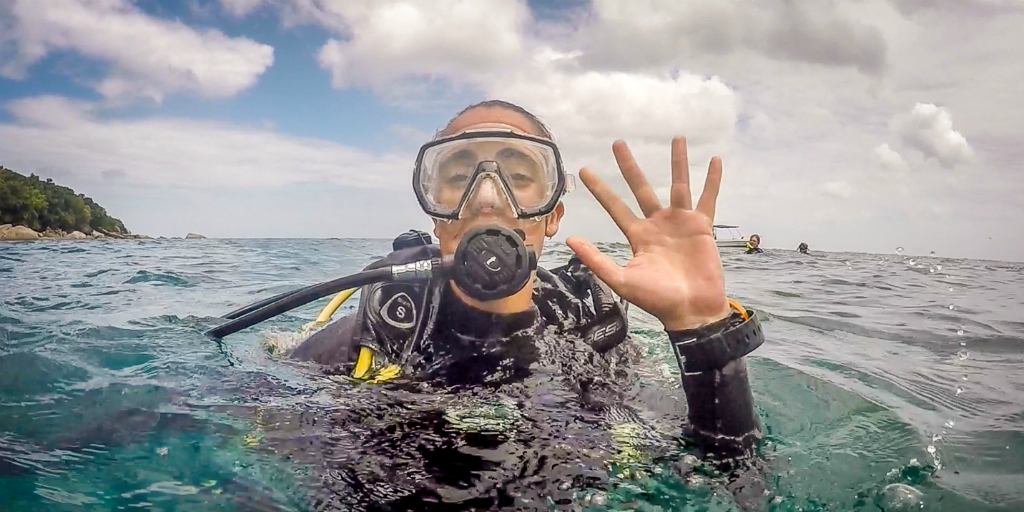 A dive training student waving from the water in full diving gear.