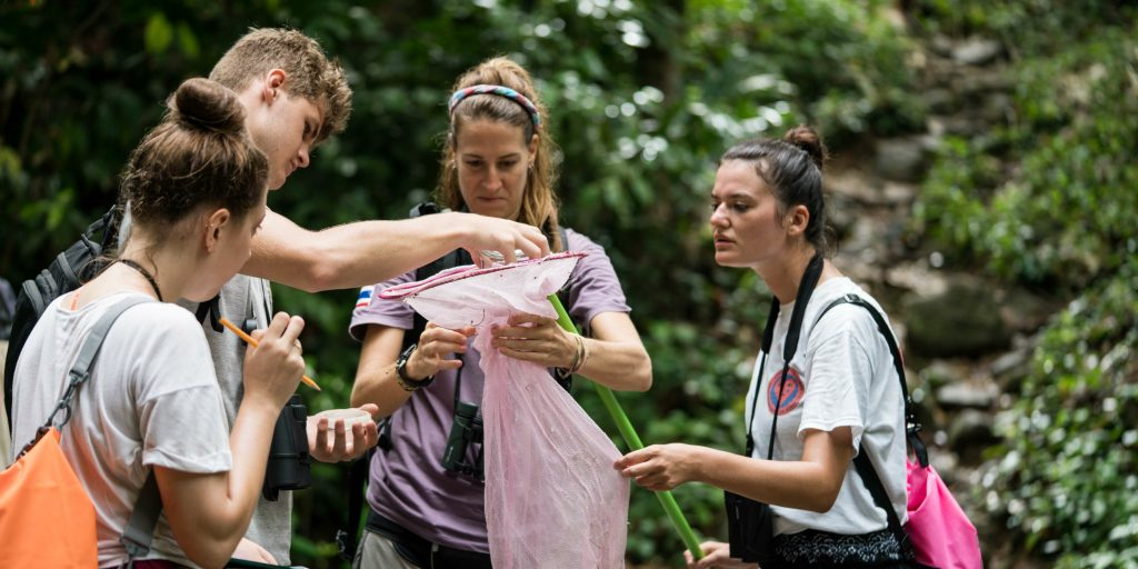 One volunteer holding a plastic bag while other volunteers fill it.