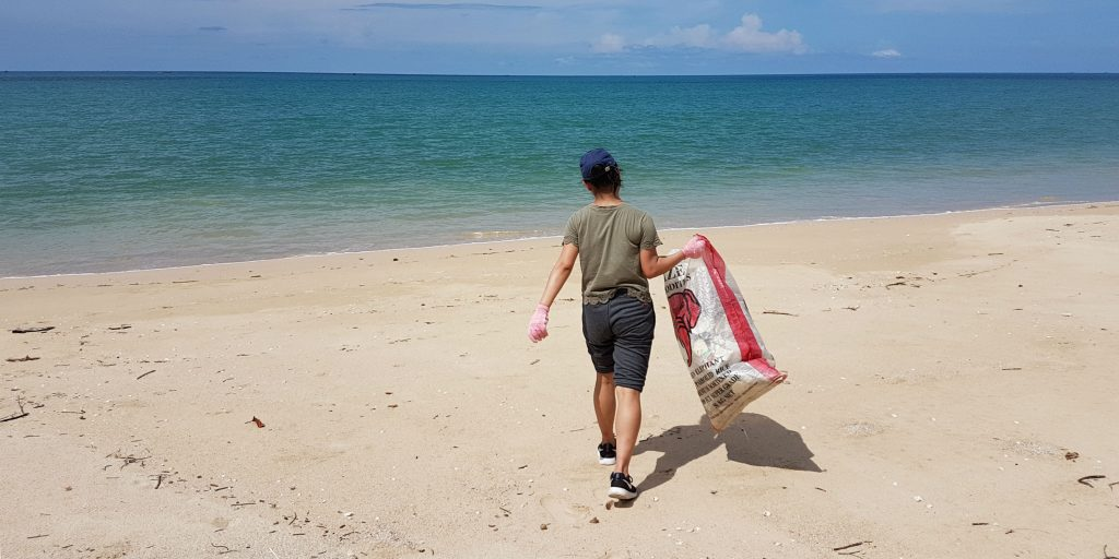 A volunteer carrying a large hessian bag across the beach.