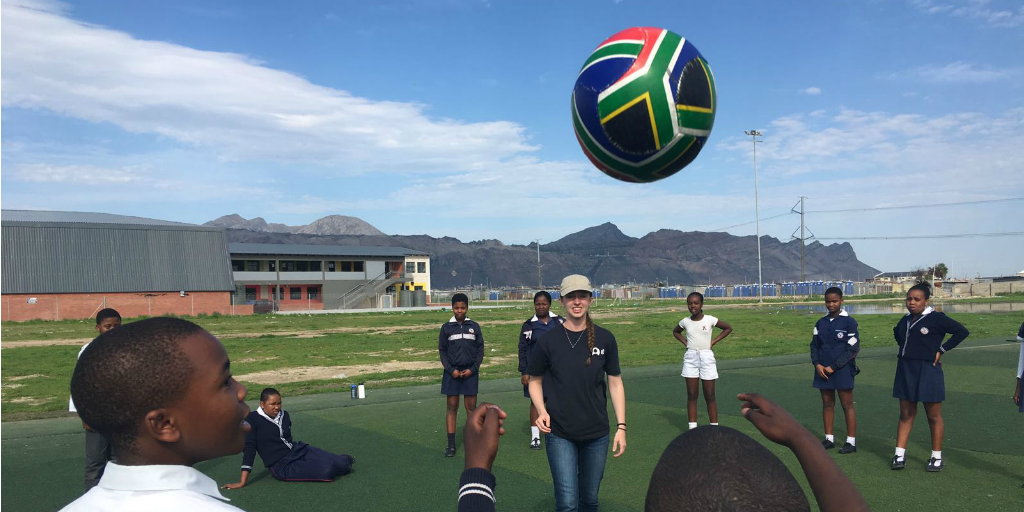 A volunteer playing soccer with children.