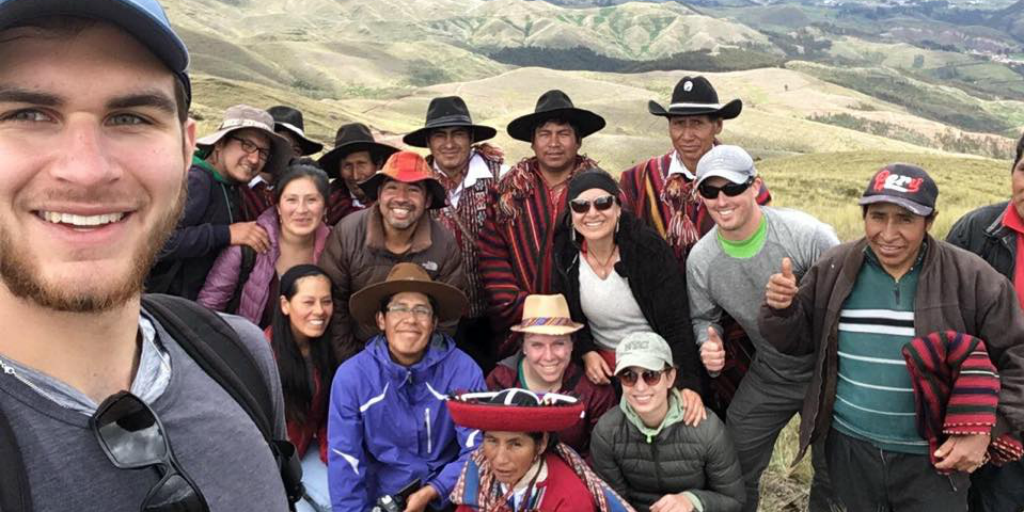 Volunteers posing for a photo with local people with a mountain range in the background.