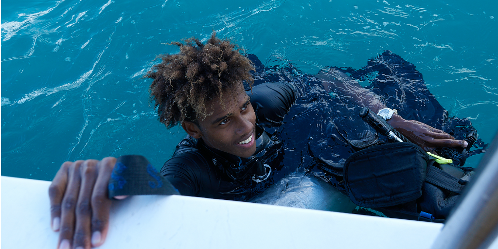 A diver holding onto the edge of a boat as he floats with his head above the surface.