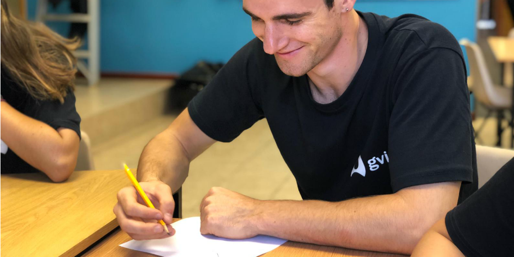 A volunteer sitting at a desk and writing on paper with a pencil.