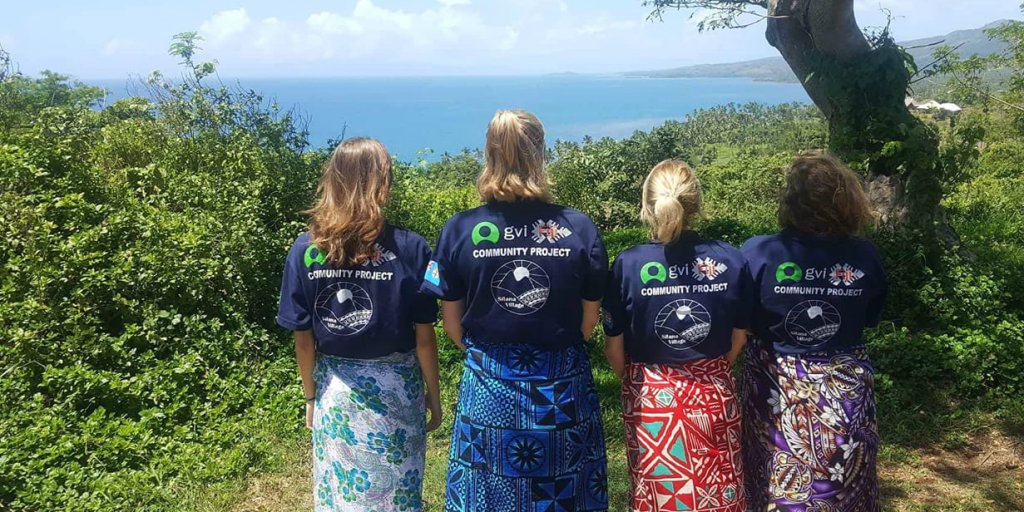 Four volunteers standing in a line and looking out over the ocean.