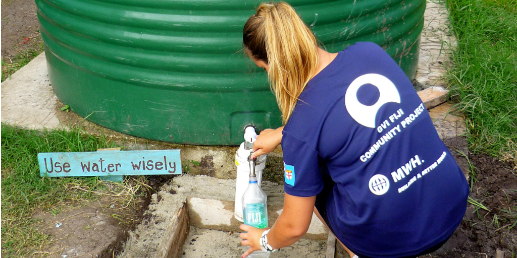 A volunteer collecting water from a rainwater collection tank.