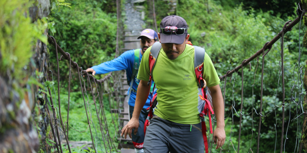 Two men walking across a suspension bridge in the jungle.
