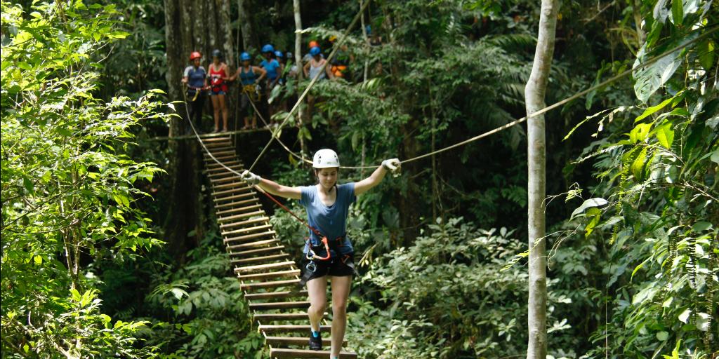 A volunteer wearing a harness, walking across a rope bridge.