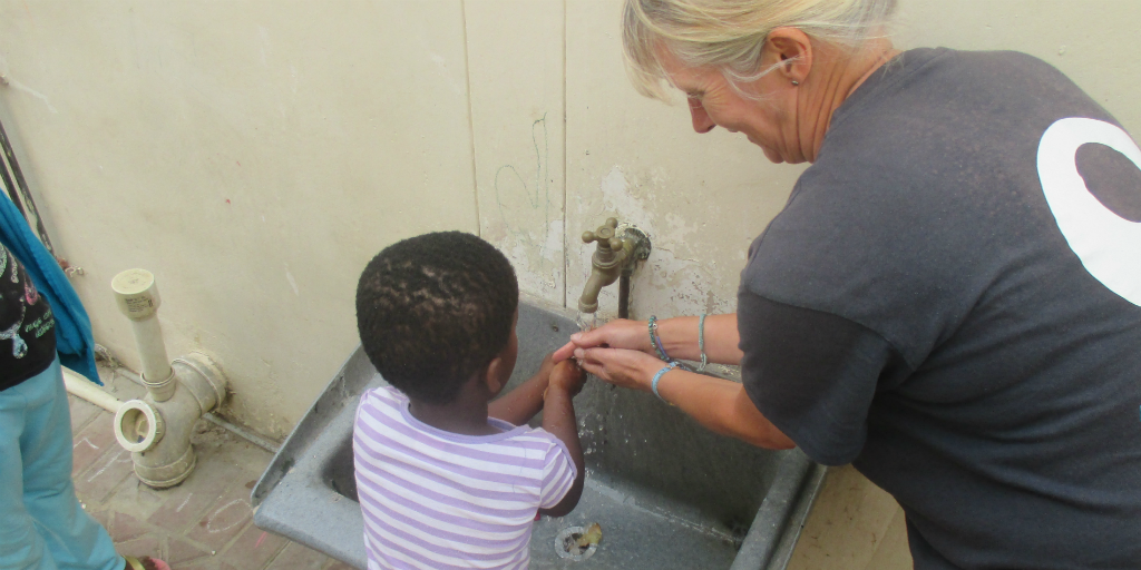 a volunteer teaches children the importance of washing your hands regularly