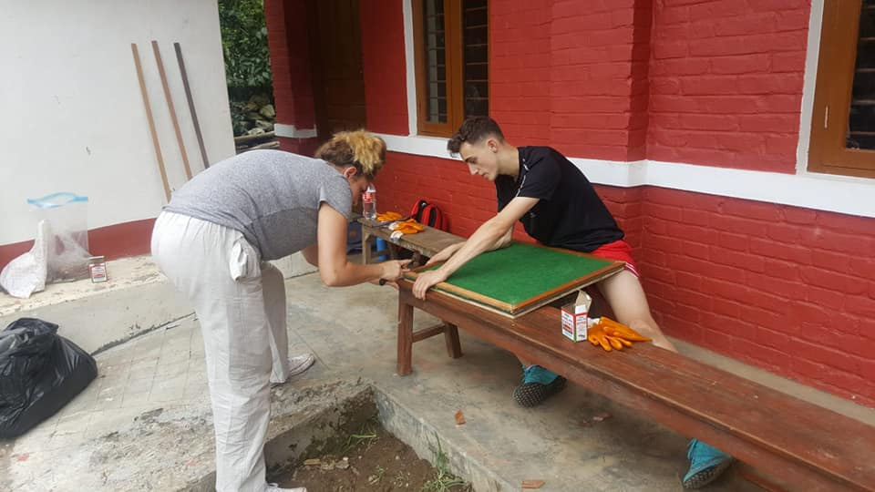 Volunteers performing construction tasks to provide schoools with the desks they need